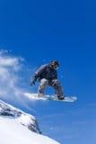 Salto masculino del snowboarder de una colina Foto de archivo libre de regalías