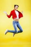 Salto moreno bonito joven de la muchacha aislado en el fondo amarillo, cierre del concepto de la gente del vuelo de la forma de v Foto de archivo libre de regalías