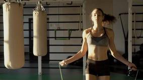 Salto moreno hermoso con la cuerda en club de deportes dentro almacen de metraje de vídeo