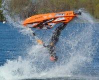 Salto mortal hacia atrás de ejecución al revés del competidor de Jet Skier del estilo libre que crea en la porción de espray Fotos de archivo
