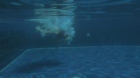 Salto mortal hacia atrás de salto de la muchacha atractiva joven en agua de lujo de la piscina el día soleado metrajes