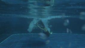 Salto mortal hacia atrás de salto de la muchacha atractiva joven en agua de lujo de la piscina el día soleado almacen de video