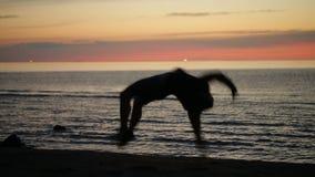 Salto mortal hacia atrás en la playa almacen de metraje de vídeo