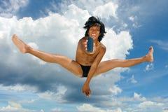 Salto muito ao alto que anuncia o telefone de pilha pelo menino tropical asiático. Foto de Stock