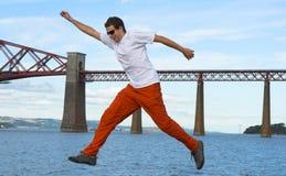 Salto o paso de progresión grande sobre el agua con el puente como fondo imagenes de archivo