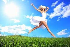 Salto para la alegría en una colina de la hierba Foto de archivo