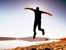 Salto pazzo dell'uomo sulla spiaggia Volo dello sportivo sulla spiaggia durante l'alba sopra l'orizzonte fotografie stock