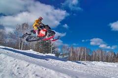 Salto rojo de la moto de nieve del deporte Día de invierno soleado claro Movimiento rápido del concepto Imágenes de archivo libres de regalías