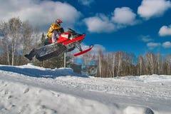 Salto rojo de la moto de nieve del deporte Día de invierno soleado con el cielo azul Movimiento rápido del concepto Imagenes de archivo