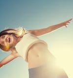 Salto rubio de la muchacha del adolescente feliz con el azul Foto de archivo