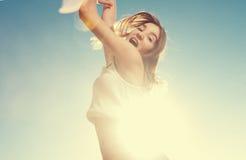Salto rubio de la muchacha del adolescente feliz con el azul Fotos de archivo libres de regalías