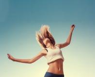 Salto rubio de la muchacha del adolescente feliz con el azul Fotografía de archivo libre de regalías