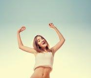 Salto rubio de la muchacha del adolescente feliz con el azul Imágenes de archivo libres de regalías