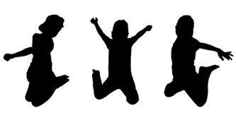 Salto silueteado de los muchachos Imagenes de archivo