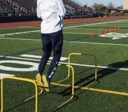 Salto sobre obstáculos amarelos durante o treinamento da velocidade Imagens de Stock