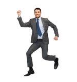 Salto sonriente del hombre de negocios Foto de archivo