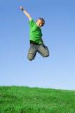 Salto sonriente feliz del niño fotografía de archivo