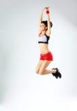 Salto sonriente joven de la mujer del deporte Fotografía de archivo