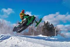 Salto verde grande de la moto de nieve del deporte Nube del polvo de la nieve de debajo pistas de la moto de nieve Imagen de archivo