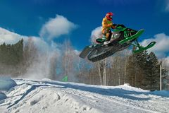 Salto verde grande de la moto de nieve del deporte Nube del polvo de la nieve de debajo pistas de la moto de nieve Resto del extr Imagenes de archivo