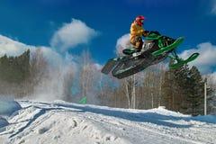Salto verde grande do carro de neve do esporte Nuvem da poeira da neve de debaixo das trilhas do carro de neve Resto do extremo d Imagens de Stock