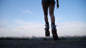 Saltos bonitos do pé em sapatas dos saltos do angoo Uma jovem mulher no short curto é contratada em esportes exteriores 4K mo len filme