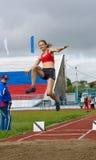Saltos de longitud de la muchacha Fotos de archivo