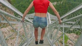 Saltos louros caucasianos novos que inclinam-se em trilhos da ponte de suspensão acima do desfiladeiro da montanha Opinião do clo filme