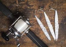 Saltwater fishing rod and lures. Saltwater fishing pole and lures on a wooden workbench stock photo