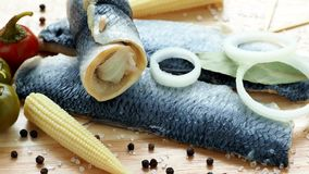 Saltwater marinated fish, cold appetizer. Herring fillet marinated. On wooden cutting board stock footage