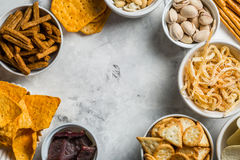 Salty beer snacks in whit bowls Royalty Free Stock Photos