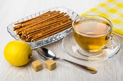 Salty breadsticks in transparent bowl, lemon, cup of tea, sugar. And teaspoon on wooden table Royalty Free Stock Image