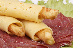 Salty cheese sticks with salami. On lettuce Stock Image