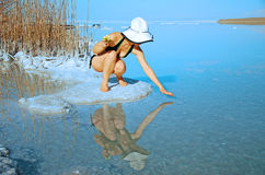 In the salty Dead Sea shore. Girl sunbathing on the beach with warm summer day Stock Photo