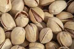 Salty delicious open pistachios in a bowl. brown natural background from natural nuts royalty free stock images