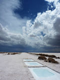 Salty desert. White salt harvesting pools in the middle of a huge salt flat. The rainy clouds already pass the Andes and are coming closer. The picture was taken royalty free stock image
