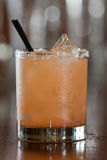 Salty dog cocktail. Closeup of a salty dog drink served in a short glass on a busy out of focus bar Royalty Free Stock Photo