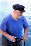 Salty Dog on the Water. A closeup of an old salty dog scruffy man wearing a wool captain's bill cap and glasses on the water with a rope in his hands.  Shallow Stock Photos