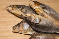 Salty dry river fish to beer on a wooden table. Stock Photos
