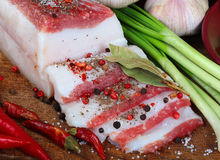 Salty fatty bacon with vegetables and spices on chopping board Stock Photography