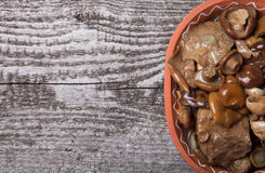 Salty mashrooms in a bowl on a old wooden board.  Stock Image