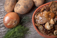 Salty mashrooms, potato, onion, dill and grain in a bowl on a ol. D wooden board Stock Photography
