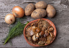 Salty mashrooms, potato, onion, dill and grain in a bowl on a ol. D wooden board Royalty Free Stock Image