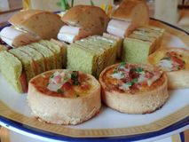 Salty pastries in English style afternoon tea. Including finger sandwich, bacon tart and ham roll, presented on a elegant porcelain dish stock photography