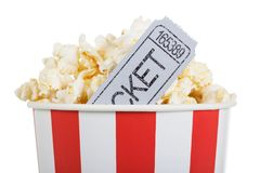Salty popcorn in box and movie ticket, isolated on white. Salty popcorn in a box and gray movie ticket, isolated on white background stock photography