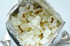 Salty popcorn in metallic packaging on white background. Salty popcorn in metallic packaging on the white background Royalty Free Stock Image