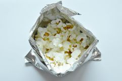 Salty popcorn in metallic packaging on white background. Salty popcorn in metallic packaging on the white background Royalty Free Stock Images