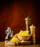 Salty Potato Chips. Salty potato-chips and ingredients, salt, oil and potato Royalty Free Stock Image