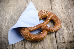 Salty pretzel with a blue napkin Royalty Free Stock Photos