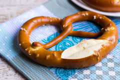 Salty pretzel on blue towel. Twisted pretzel on a towel on the table Stock Photography